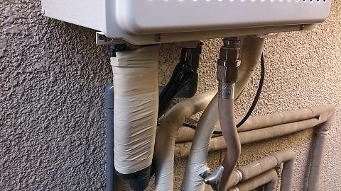 エコジョーズ給湯器の配管写真です。ドレンを排水する塩ビ管が見えます。